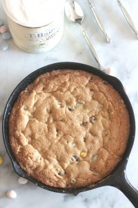 This deep dish chocolate chip cookie with Cadbury Mini Eggs is a heavenly Easter treat. Topped with vanilla ice cream and served warm, it's a dessert everyone will love!