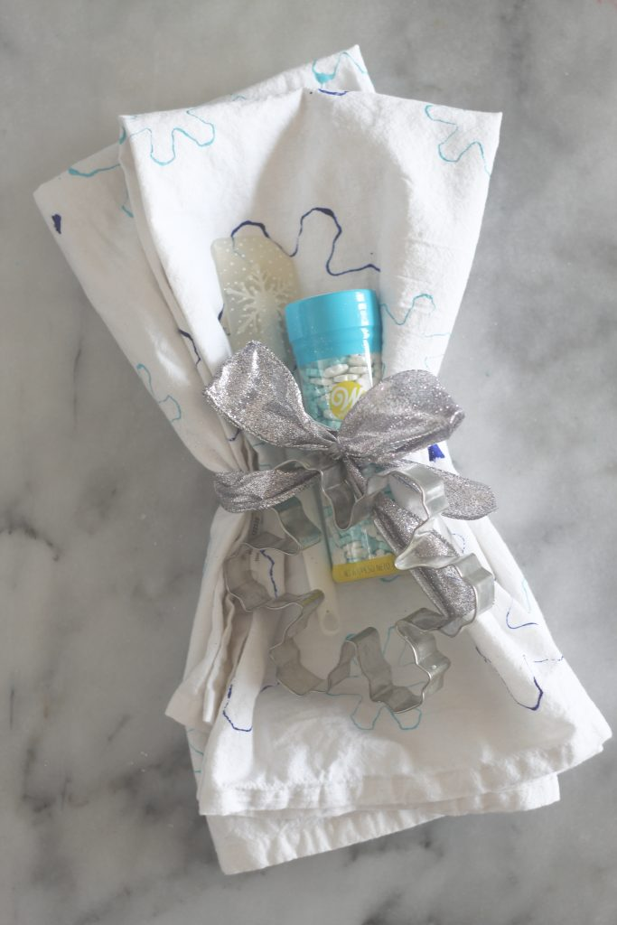 Take 10 minutes out of your day to make these DIY kitchen towels with some paint and cookie cutters! #homemadegifts #handmadeholidays #DIYChristmas #Christmas #Christmascrafts #sparkleliving #snowflakecrafts #cookiecuttercrafts #12daysofChristmas