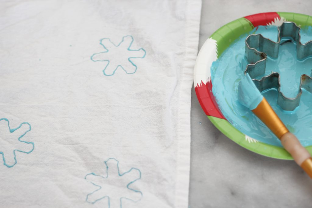 Take 10 minutes out of your day to make these DIY kitchen towels with some paint and cookie cutters! #homemadegifts #handmadeholidays #DIYChristmas #Christmas #Christmascrafts #sparkleliving #snowflakecrafts #cookiecuttercrafts 312daysofChristmas