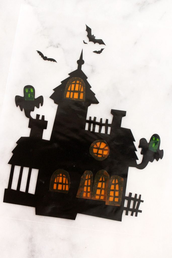 Adhesive vinyl from StyleTech Craft for Halloween Haunted House Pillar Candle Craft. Backside of vinyl on transfer paper.