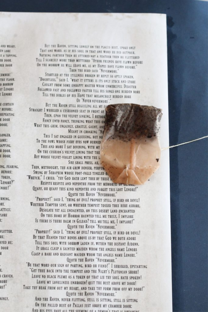 Staining the paper with the poem printed with tea to age it.