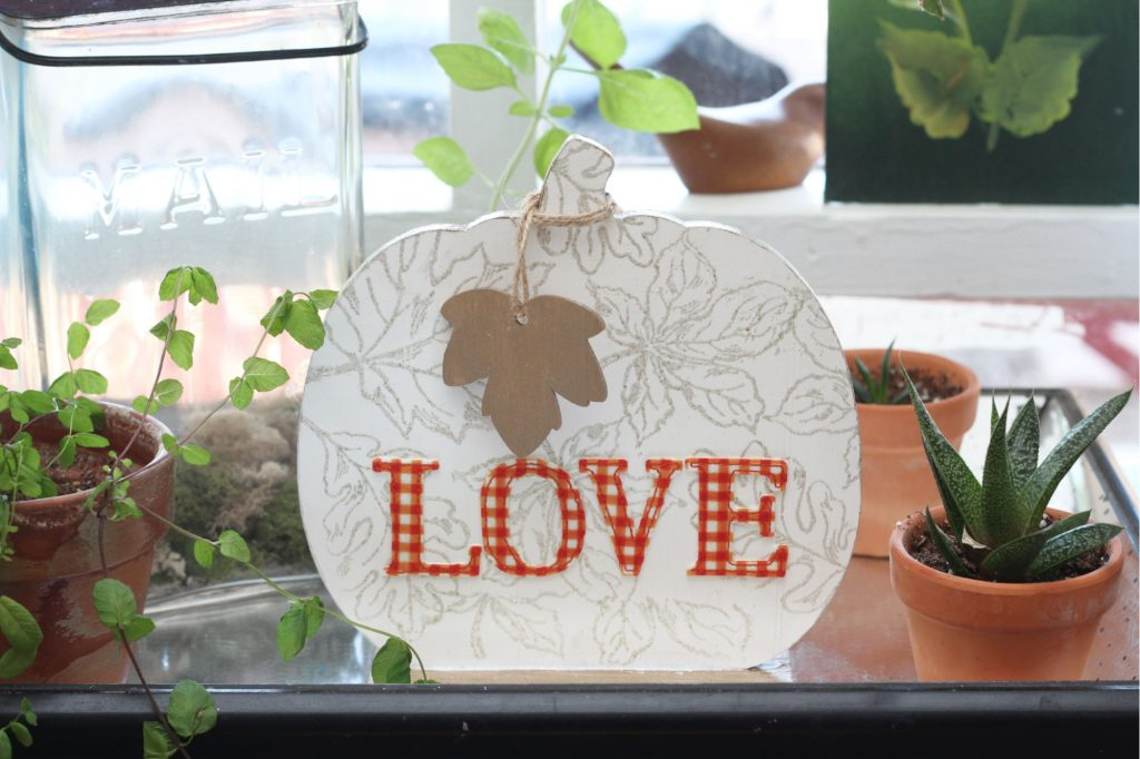 Tutorial for painted wooden pumpkin sign, embossed with leaf outlines and an orange, fabric, iron-on appliqué that says love.