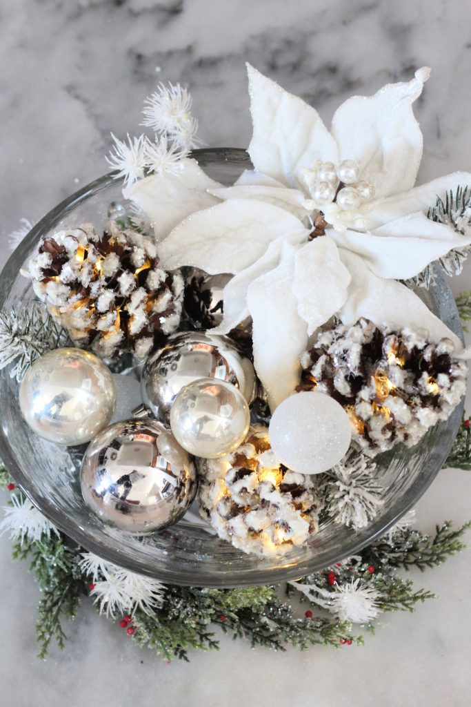 snowy lighted pinecones in centerpiece with christmas balls and poinsettia in a bowl
