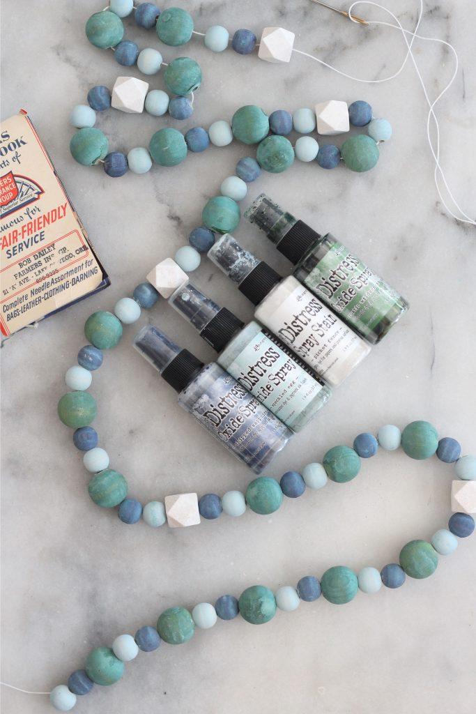 wood bead garland with distress oxide sprays.