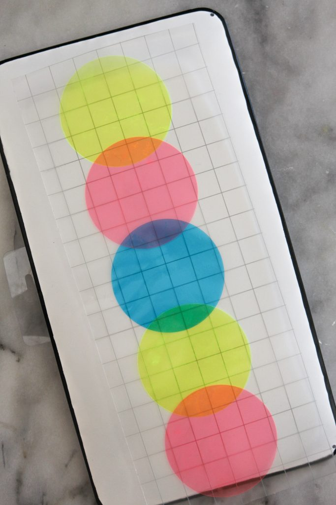 Using the gridded transfer tape to adhere the colorful vinyl circles.