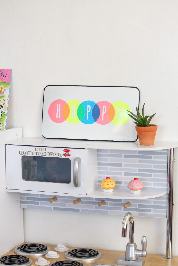 colorful vinyl happy sign sitting on play kitchen