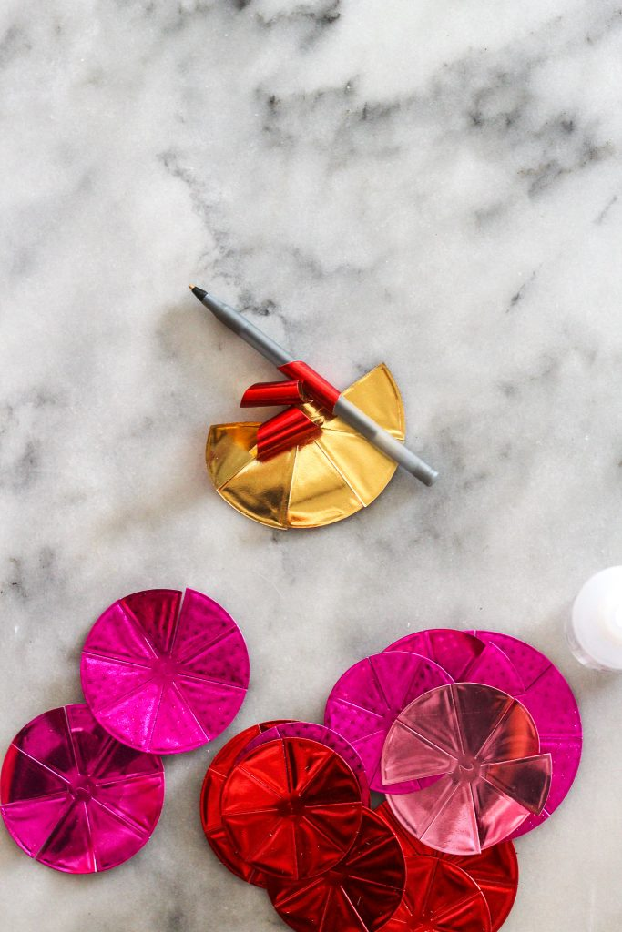 Rolling foiled paper roses with pencil