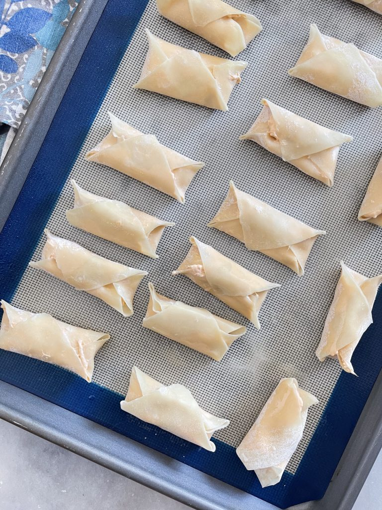 Uncooked Buffalo Chicken Won Ton Dippers on baking sheet.
