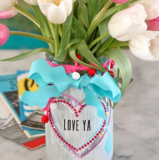 Canning jar vase painted white with colorful vinyl hearts.