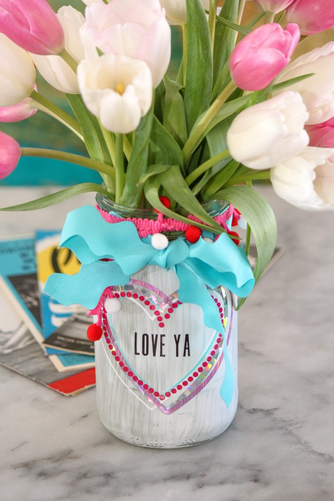 Canning jar vase painted white with colorful vinyl hearts filled with pink and white tulips