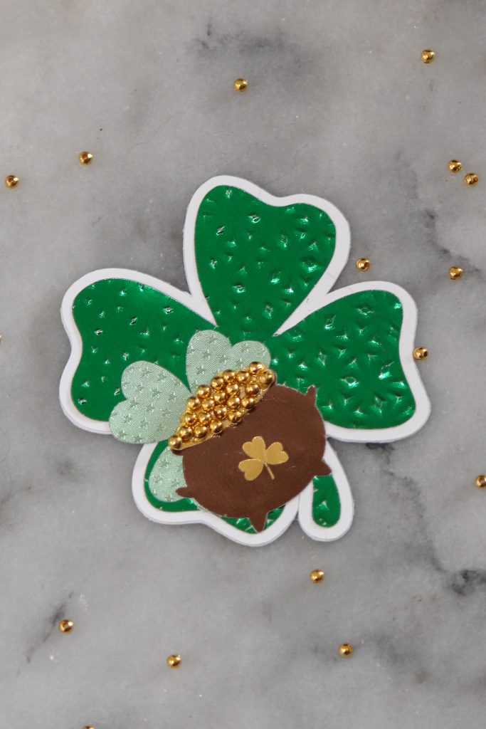 Shamrock shaped gift tag with a pot of gold on it.