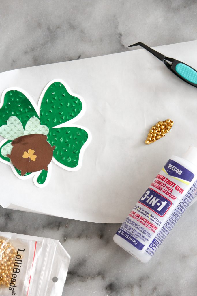Shamrock gift tag assembly with gold beads and glue.