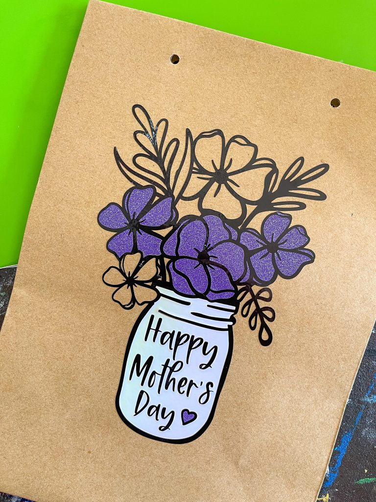 Mother's Day gift bag with black vinyl outline and some of the purple flowers adhered on.