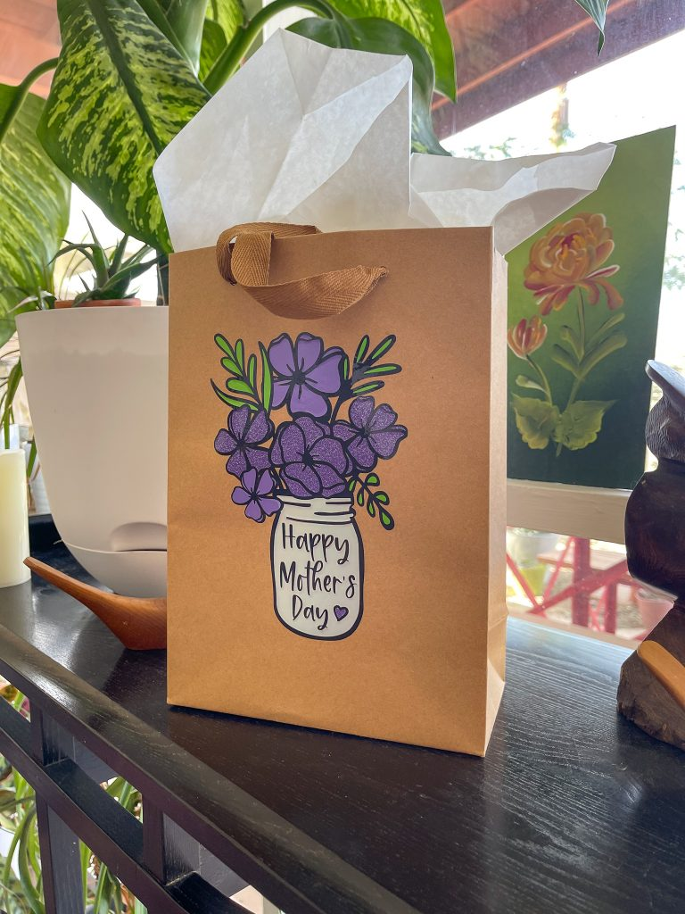 Mother's Day gift bag with tissue paper on table.