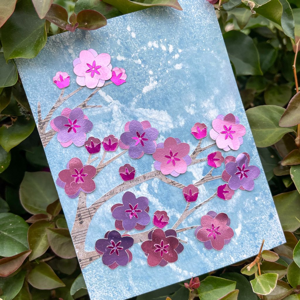 Square image of cherry blossom card with leaves in the background.