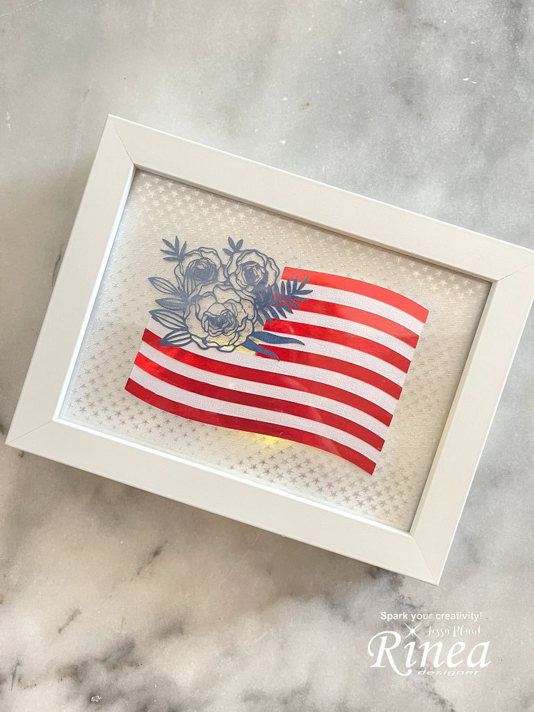 this image depicts the finished lighted 4th of july flag art with flowers  in place of the stars on the flag.