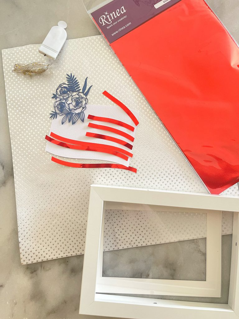 This image depicts supplies for the project, mini lights, Rinea foiled paper pack in red, and silver starstruck, a picture frame and the cut out paper.