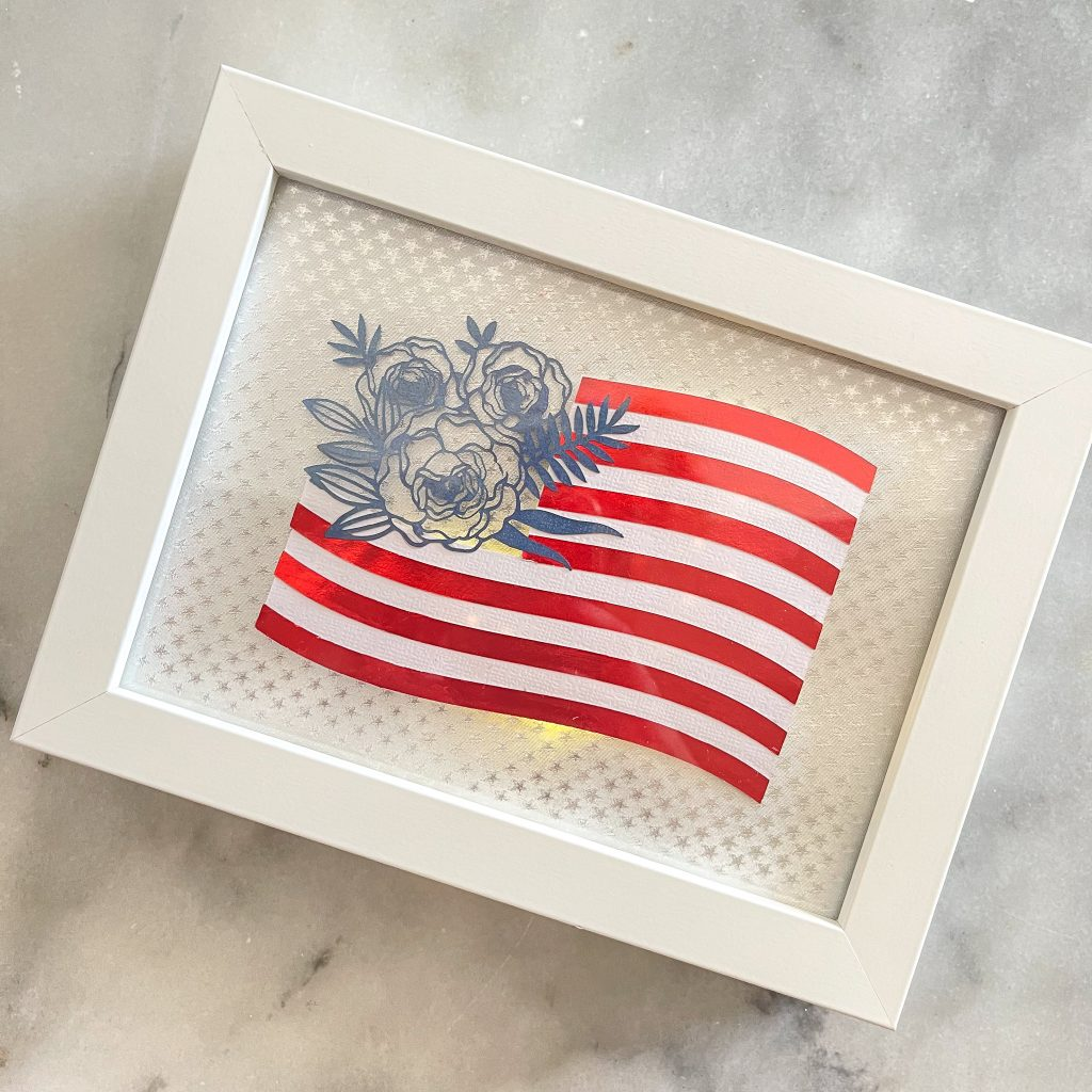 lighted american flag with flowers in a frame.
