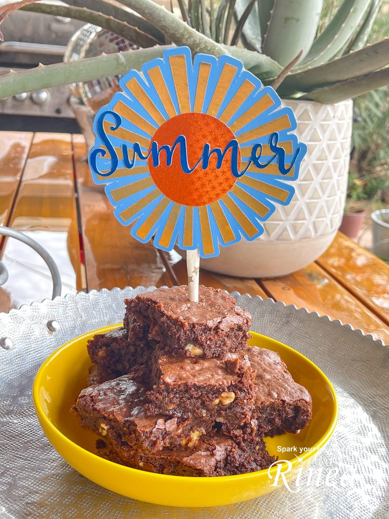 This image is a close up of the summer cake topper in the yellow bowl of brownies.