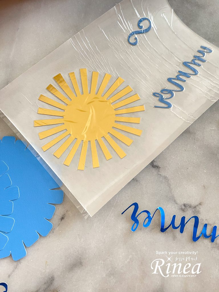 This image shows the foiled paper sun cut out and the word summer cut out after going through the Xyron creative station for adhesive.