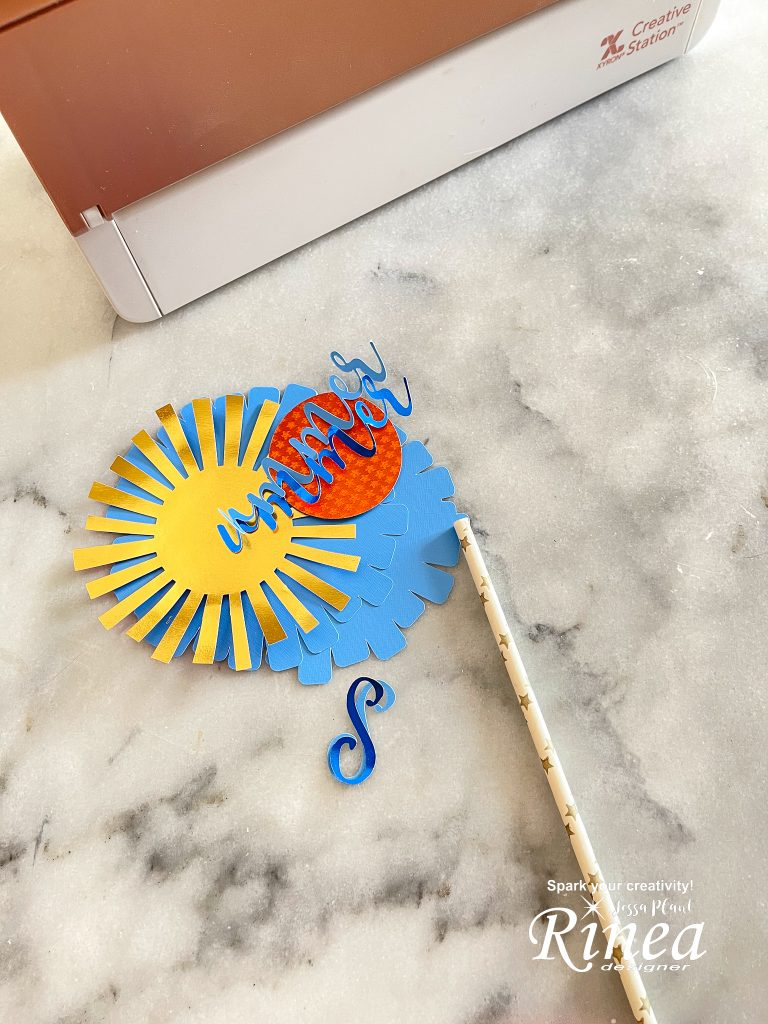 This image shows the cut outs of all the pieces of the summer cake topper, a paper straw and the Xyron creative station in the background.