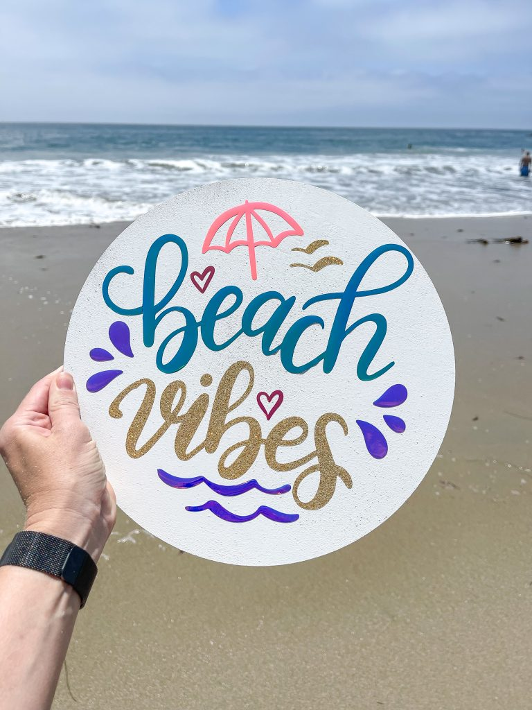 Image depicts beach vibes sign with ocean in the background.