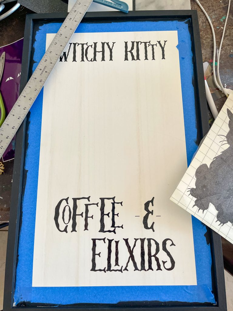 This image depicts the witchy kitty coffee sign being put together with the vinyl words attached and the T-square on top of it.