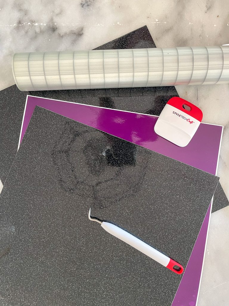 Image depicts adhesive vinyl in black Galaxy Glitter and Transparent purple vinyl. It also shows transfer tape a picking tool and a smoothing tool that has Styletech Craft printed on it.
