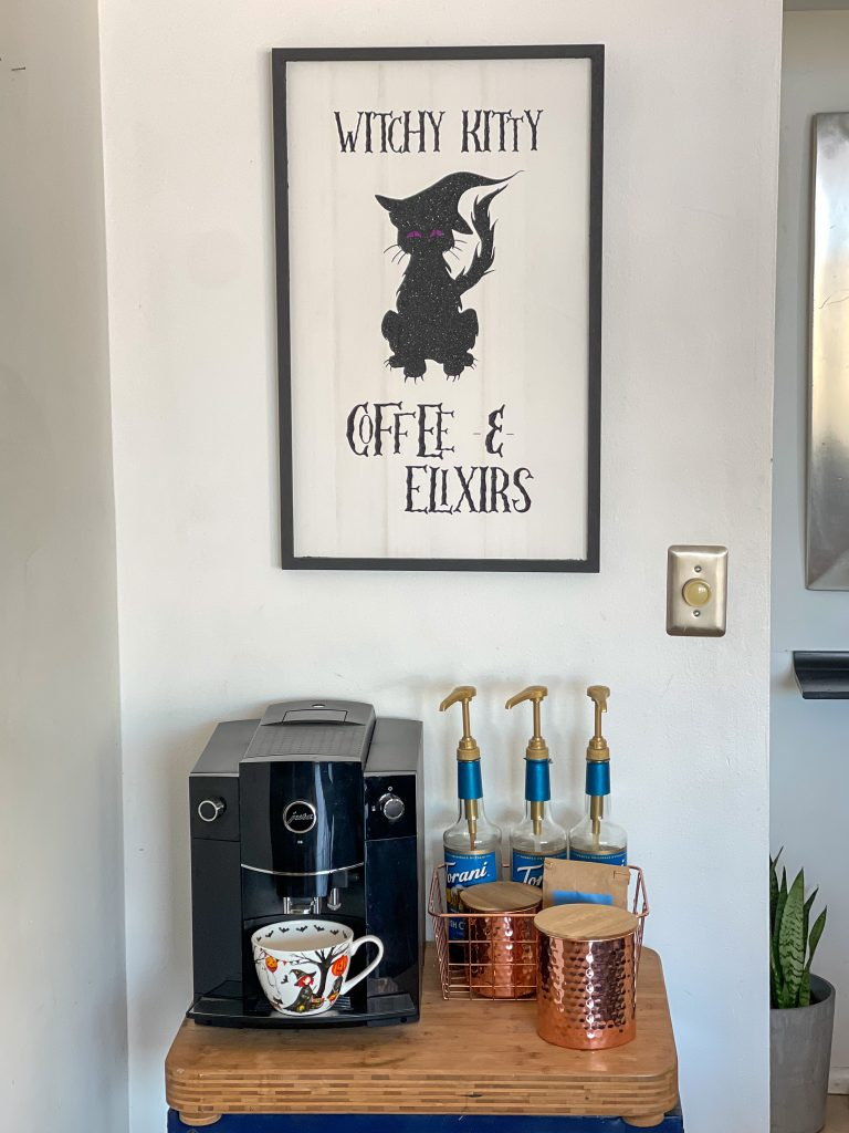This image depicts the Halloween Black Cat Coffee and Elixirs sign on a wall above a coffee station with a coffee machine with a Halloween mug in in and flavored syrups.