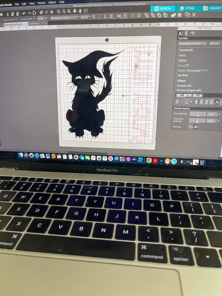 Image depicts the Silhouette software on a MacBook laptop with the black cat being sized on the screen.