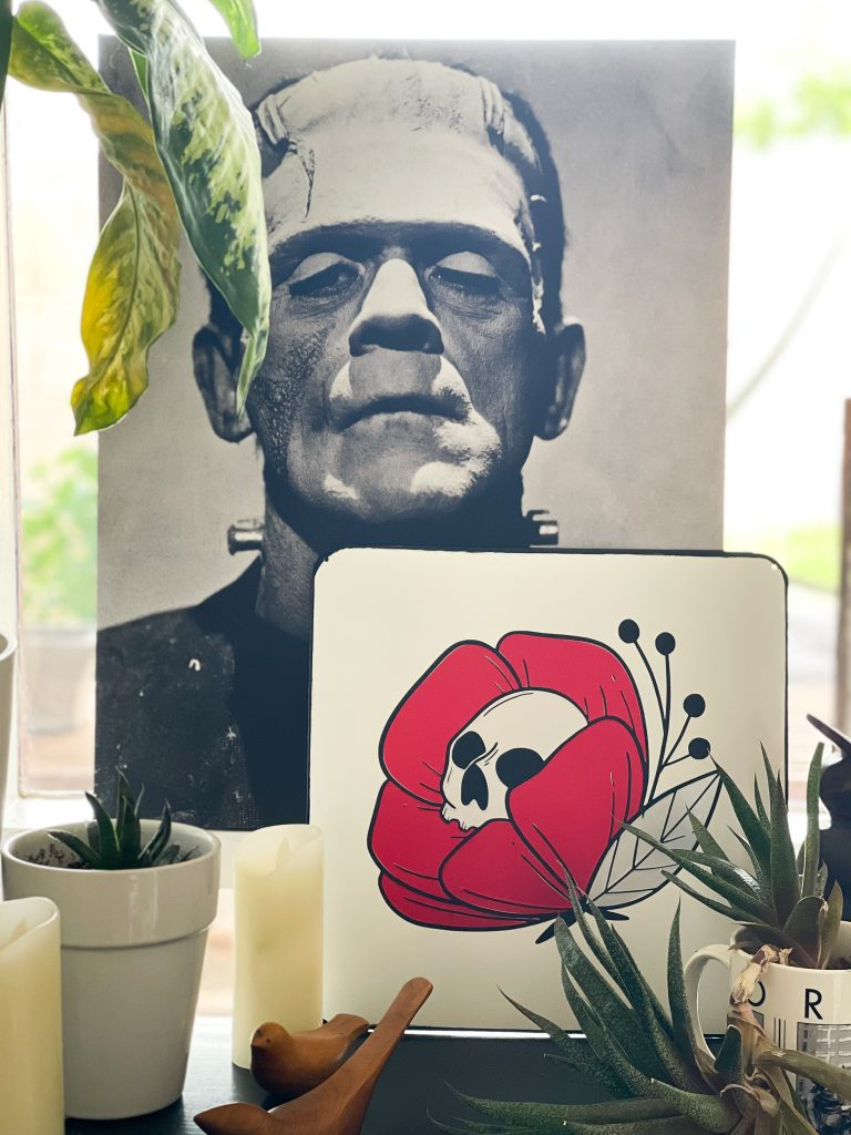 skull flower halloween sign on a black table with a black and white canvas of Frankenstein in the background.