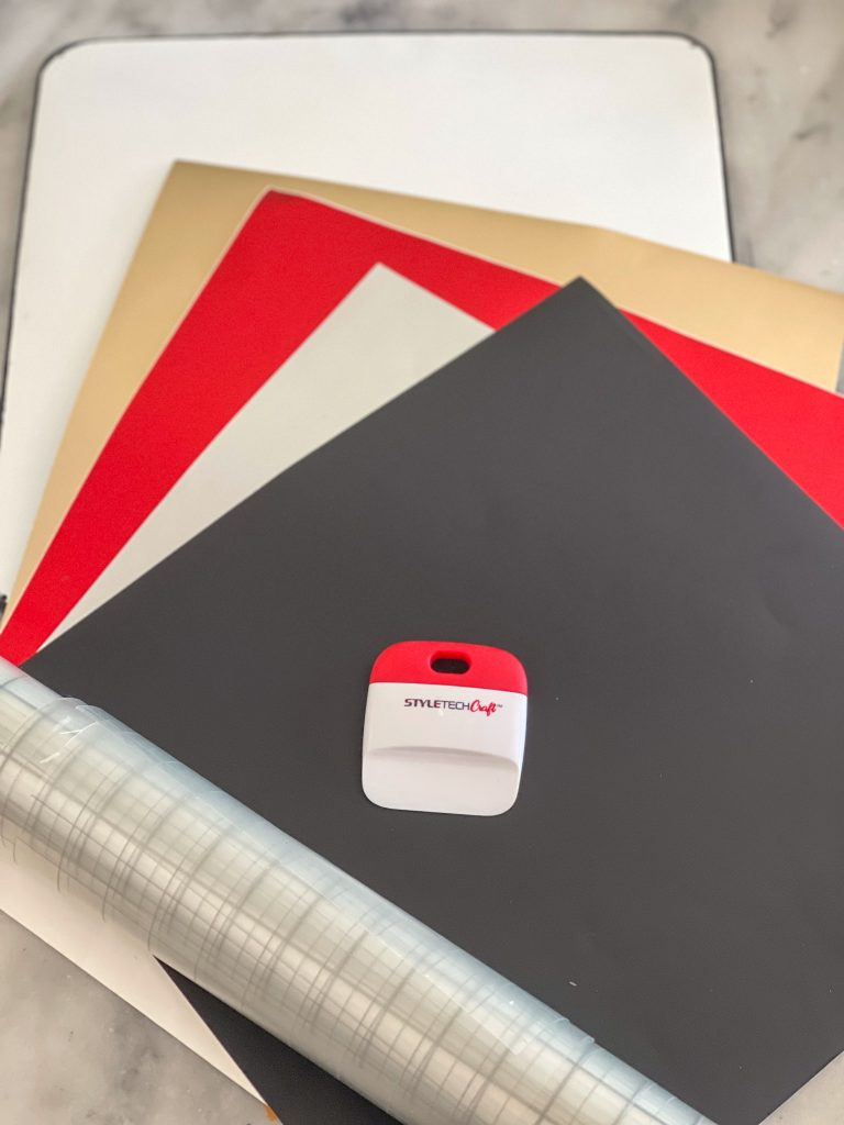 Black, red, silver and gold adhesive vinyl with a role of transfer tape and a smoothing tool on a grey background.